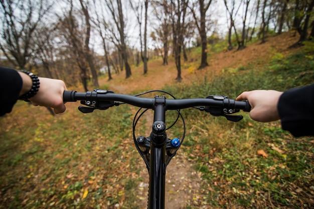 Close-upbeeld van de handen van de fietsermens op fiets van de stuur de berijdende berg op sleep in de herfstpark