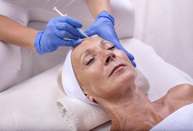 Close-upbeeld van de handen van de schoonheidsspecialist die een injectie in een vrouwelijk gezicht doen
