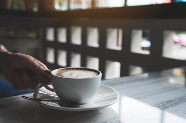 Close-upbeeld van de handen van de vrouw die een kop van hete koffie met hart latte kunst houden op lijst in koffie