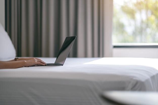 Close-upbeeld van de handen van een vrouw die op laptop computer op het bed gebruiken en typen
