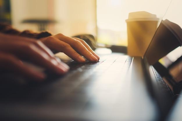 Close-upbeeld van de handen van een vrouw die werken en typen op een laptopcomputer op tafel