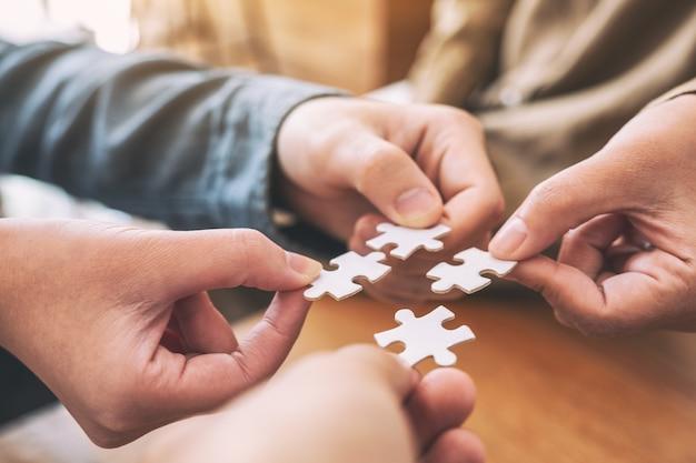 Close-upbeeld van de handen van mensen die een stukje witte puzzel vasthouden en in elkaar zetten