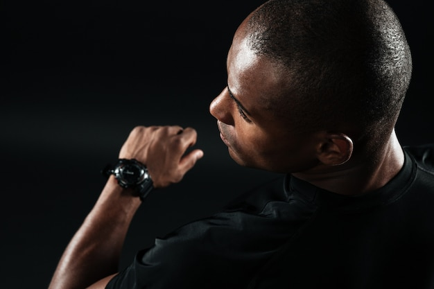 Close-upbeeld van de jonge afro amerikaanse mens gekleed in zwarte t-shirt