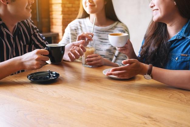 Close-upbeeld van drie mensen die genoten hebben van praten en samen koffie drinken in café