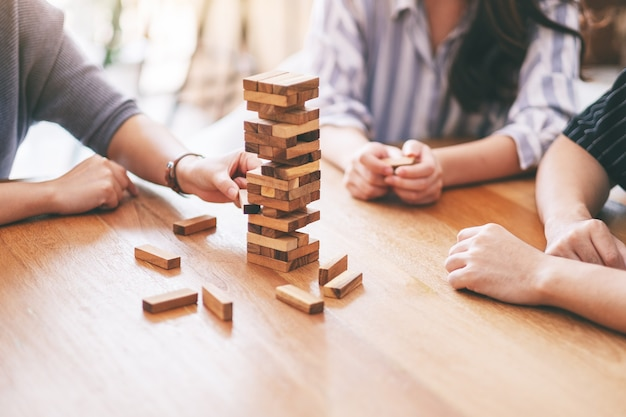 Close-upbeeld van drie vrienden die samen tumble tower houten blokspel zitten en spelen
