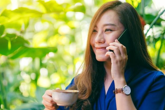 Close-upbeeld van een aziatische vrouw die een mobiele telefoon vasthoudt en praat terwijl ze koffie drinkt in de tuin