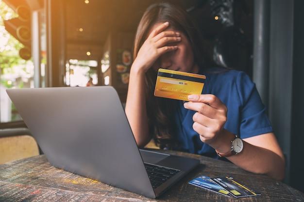 Close-upbeeld van een aziatische vrouw die gestrest en kapot gaat terwijl ze een creditcard met een laptop op tafel houdt