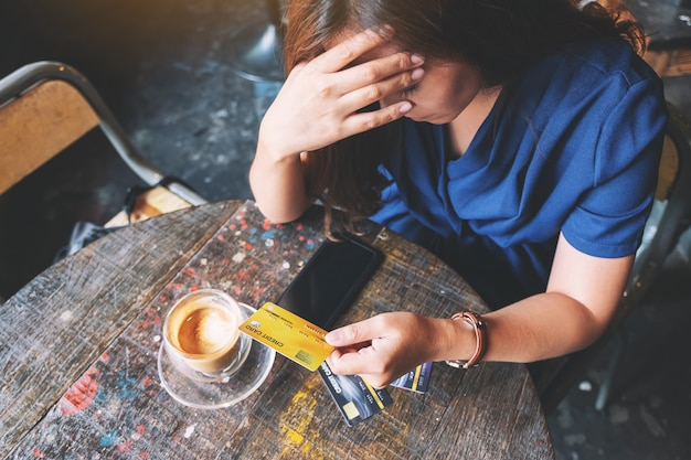 Close-upbeeld van een aziatische vrouw die gestrest raakt en kapot gaat terwijl ze een creditcard vasthoudt