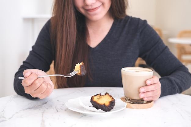 Close-upbeeld van een de koffiekop van de vrouwenholding en het eten van dessert in moderne koffie
