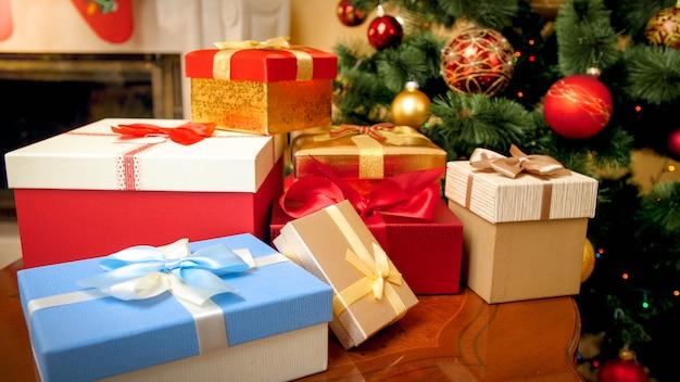 Close-upbeeld van een grote hoop kleurrijke kerstcadeaudozen en cadeautjes tegen een versierde kerstboom met slingers en ballen