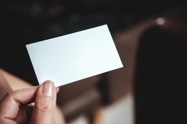Close-upbeeld van een hand die leeg adreskaartje in bureau houdt