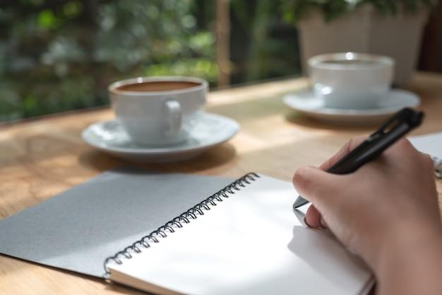 Close-upbeeld van een hand die op een wit leeg notitieboekje met koffiekop neerschrijven op houten lijst