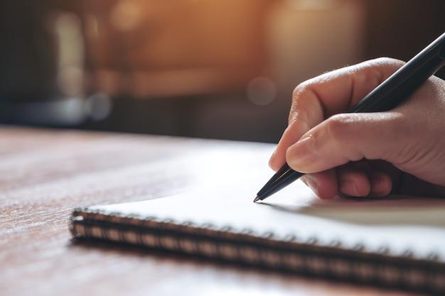 Close-upbeeld van een hand die op een wit leeg notitieboekje op houten lijst neerschrijven