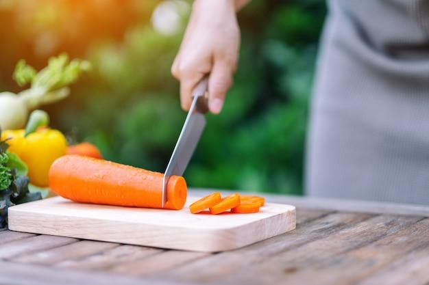 Close-upbeeld van een hand die wortel snijdt en hakt met een mes op een houten bord