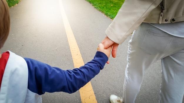Close-upbeeld van een kleine 3 jaar oude peuterjongen die zijn moeder met de hand vasthoudt en in het park op de weg loopt