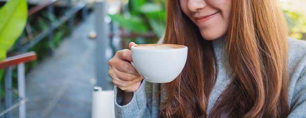 Close-upbeeld van een mooie aziatische vrouw die een kop hete koffie houdt om te drinken