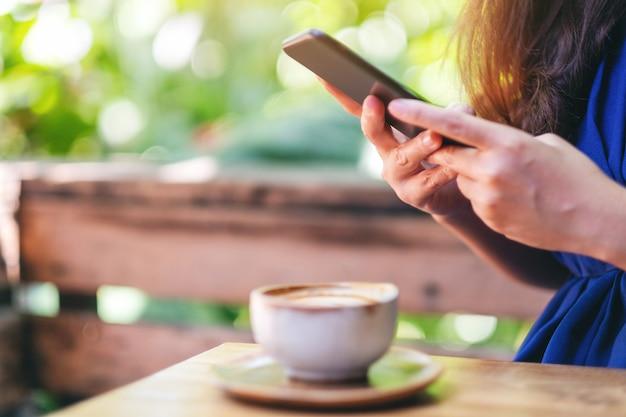 Close-upbeeld van een mooie aziatische vrouw die een mobiele telefoon vasthoudt en gebruikt met een koffiekopje op de tafel in de tuin