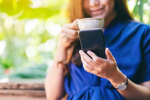 Close-upbeeld van een mooie aziatische vrouw die een mobiele telefoon vasthoudt en gebruikt terwijl ze koffie drinkt in de tuin