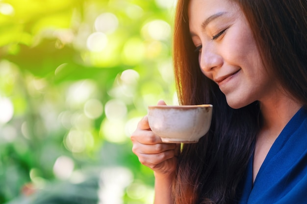 Close-upbeeld van een mooie aziatische vrouw die hete koffie in de tuin houdt en drinkt
