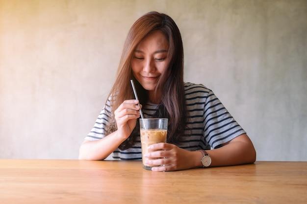 Close-upbeeld van een mooie aziatische vrouw die ijskoffie drinkt met roestvrijstalen rietje