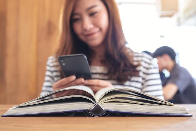 Close-upbeeld van een mooie aziatische vrouw die slimme telefoon met een boek op houten lijst houdt, gebruikt en bekijkt