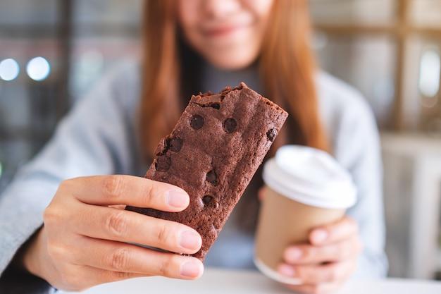 Close-upbeeld van een mooie vrouw die een stuk browniecake vasthoudt en eet terwijl ze koffie drinkt