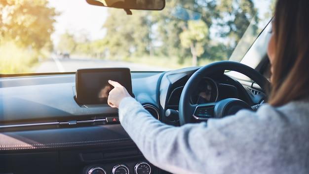 Close-upbeeld van een mooie vrouw die met de vinger naar het navigatiescherm wijst tijdens het autorijden