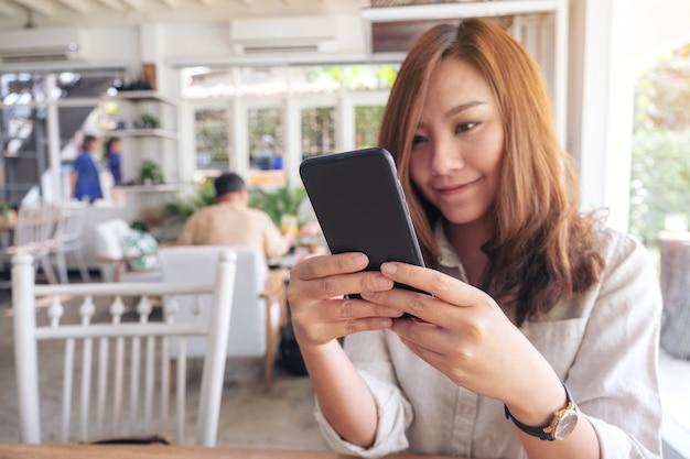 Close-upbeeld van een mooie vrouw die slimme telefoon in koffie houdt, gebruikt en bekijkt