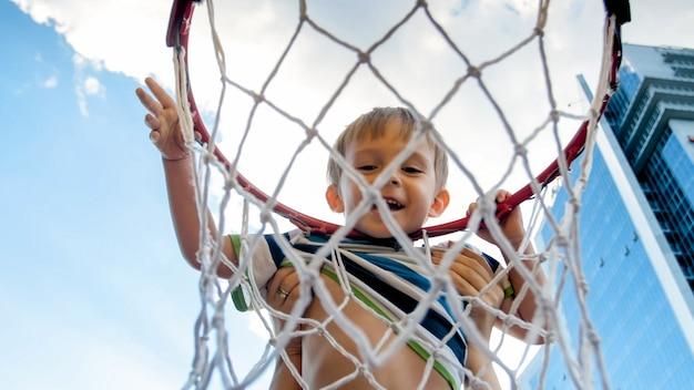 Close-upbeeld van een schattige lachende peuterjongen die een basketbalring vasthoudt en hangt op de speelplaats van sporters in de stad Premium Foto