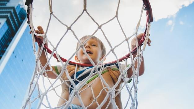Close-upbeeld van een schattige lachende peuterjongen die een basketbalring vasthoudt en hangt op de speelplaats van sporters in de stad