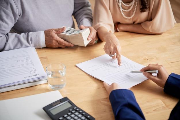 Close-upbeeld van een senior koppel dat het formulier voor een verkoopakte invult en een aanbetaling doet voor een nieuw huis
