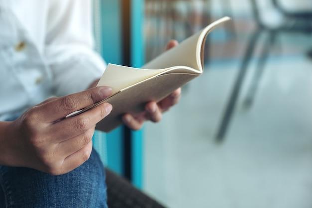 Close-upbeeld van een vrouw die een boek houdt en leest