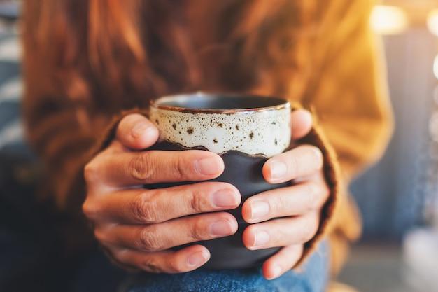 Close-upbeeld van een vrouw die een kop hete koffie houdt