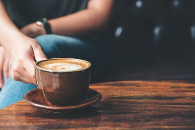 Close-upbeeld van een vrouw die een kopkoffie op uitstekende houten lijst in koffie houden