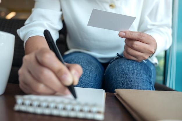 Close-upbeeld van een vrouw die een leeg leeg adreskaartje houdt tijdens het schrijven op een notitieboekje