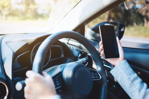 Close-upbeeld van een vrouw die een mobiele telefoon gebruikt tijdens het autorijden