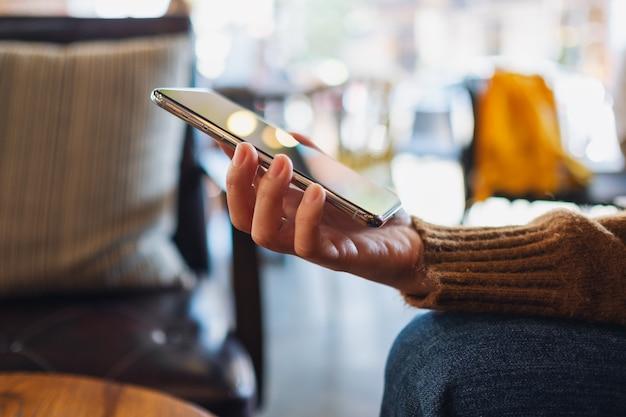 Close-upbeeld van een vrouw die een mobiele telefoon vasthoudt en gebruikt
