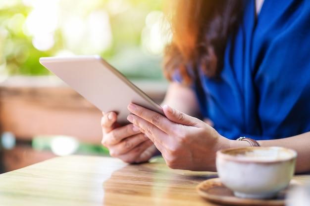 Close-upbeeld van een vrouw die een tablet-pc vasthoudt en gebruikt met een koffiekopje op tafel