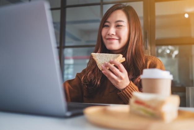 Close-upbeeld van een vrouw die een volkoren sandwich vasthoudt en eet terwijl ze op een laptop werkt