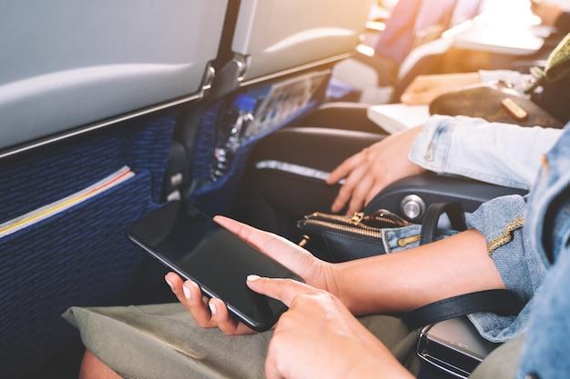 Close-upbeeld van een vrouw die en op het scherm van een zwarte slimme telefoon vasthoudt terwijl hij in de cabine zit