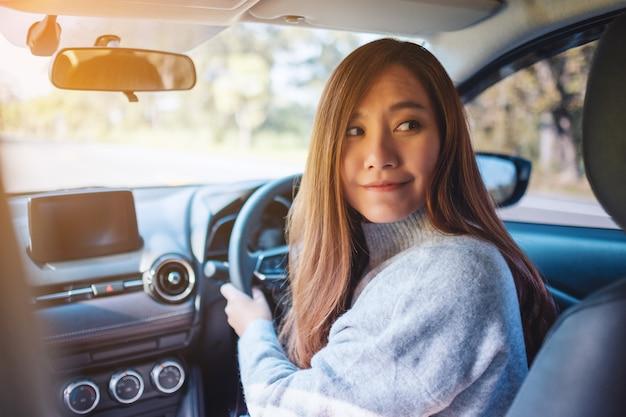 Close-upbeeld van een vrouw die het stuur vasthoudt en achterom kijkt terwijl ze achteruit op de weg rijdt