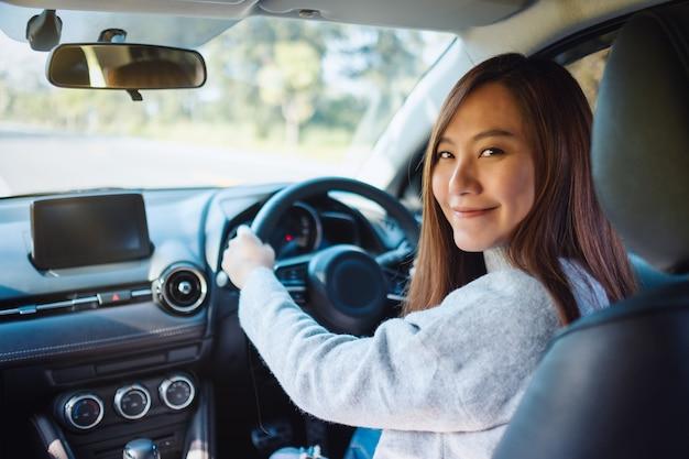 Close-upbeeld van een vrouw die het stuur vasthoudt terwijl ze een auto op de weg bestuurt