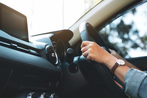 Close-upbeeld van een vrouw die het stuur vasthoudt tijdens het autorijden