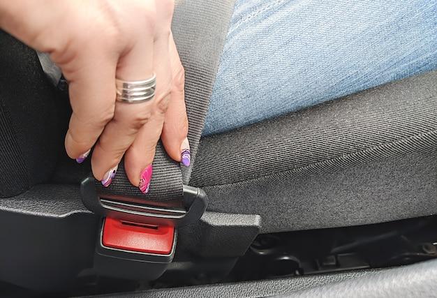 Close-upbeeld van een vrouw die in auto zit en haar veiligheidsgordel, het veiligheidsconcept drijft