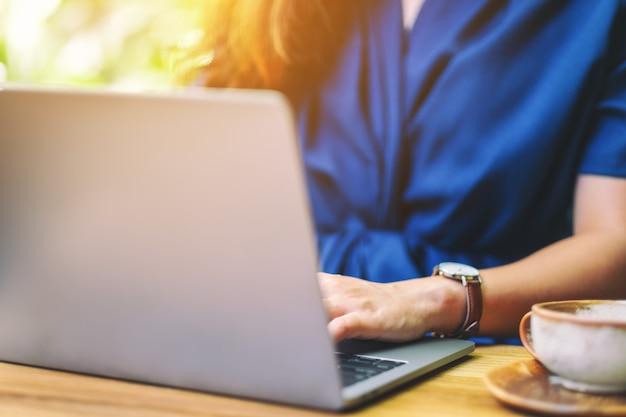 Close-upbeeld van een vrouw die laptopcomputer in de buitenlucht werkt en gebruikt