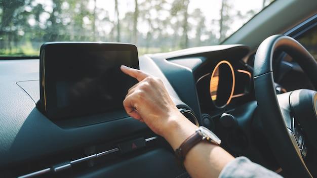Close-upbeeld van een vrouw die met de vinger naar het navigatiescherm wijst tijdens het autorijden