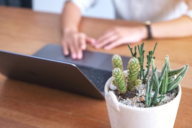 Close-upbeeld van een vrouw die op laptop computer touchpad met cactuspot op houten lijst gebruiken en aan te raken