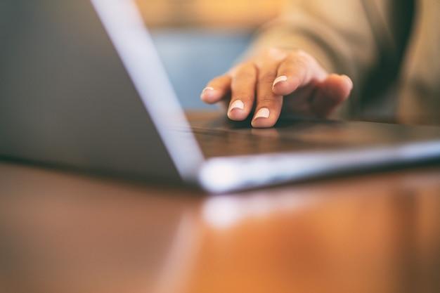 Close-upbeeld van een vrouw die op laptop computer touchpad op houten lijst gebruiken en aan te raken