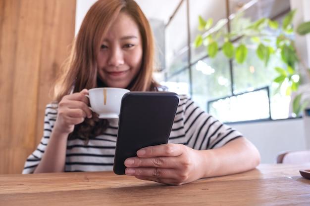 Close-upbeeld van een vrouw die slimme telefoon houdt, gebruikt en bekijkt terwijl het drinken van koffie