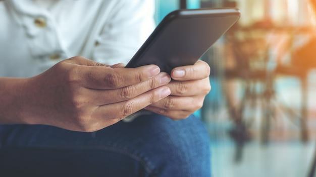 Close-upbeeld van een vrouw die slimme telefoon in koffie houdt, gebruikt en bekijkt